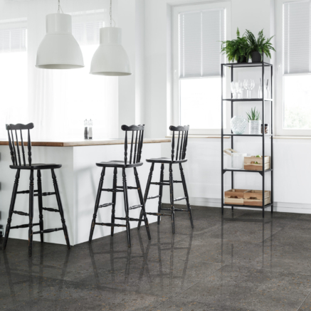 Bright rustic living room with black bar stools and white design lamp and above kitchenette